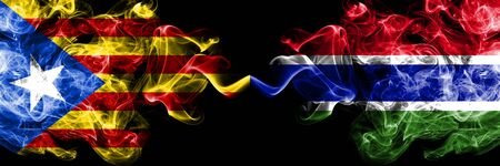Catalonia vs Gambia, Gambian smoke flags placed side by side. Thick colored silky smoke flags of Catalonia and Gambia, Gambian Foto de archivo