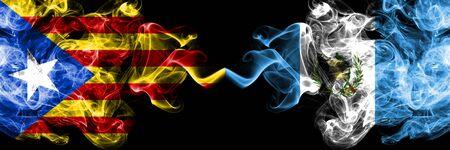 Catalonia vs Guatemala, Guatemalan smoke flags placed side by side. Thick colored silky smoke flags of Catalonia and Guatemala, Guatemalan Foto de archivo
