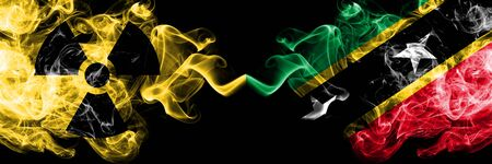 Saint Kitts and Nevis vs nuclear smoky mystic flags placed side by side. Thick colored silky smokes combination of Saint Kitts and Nevis flag and radioactive sign.