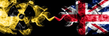 United Kingdom, British vs nuclear smoky mystic flags placed side by side. Thick colored silky smokes combination of United Kingdom, British flag and radioactive sign. Stock Photo