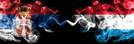 Serbia vs Luxembourg smoky mystic flags placed side by side. Thick colored silky smokes combination of Serbian and Luxembourg flag Standard-Bild