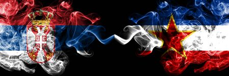Serbia vs Yugoslavia smoky mystic flags placed side by side. Thick colored silky smokes combination of Serbian and Yugoslavia flag Standard-Bild