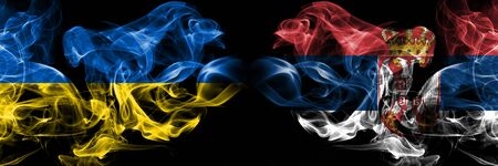 Ukraine, Serbia, flip competition thick colorful smoky flags. European football qualifications games