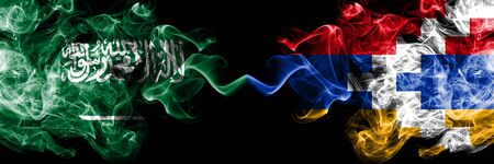 Saudi Arabia Kingdom vs Artsakh smoky mystic flags placed side by side. Thick colored silky smoke flags of Arabic, Arabian and Artsakh