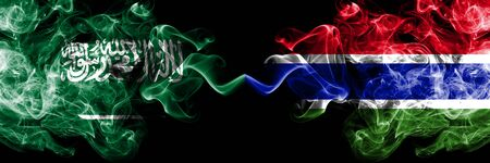 Saudi Arabia Kingdom vs Gambia, Gambian smoky mystic flags placed side by side. Thick colored silky smoke flags of Arabic, Arabian and Gambia, Gambian Banco de Imagens