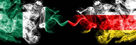 Nigeria vs South Ossetia abstract smoky mystic flags placed side by side. Thick colored silky smoke flags of Nigerian and South Ossetia Banco de Imagens
