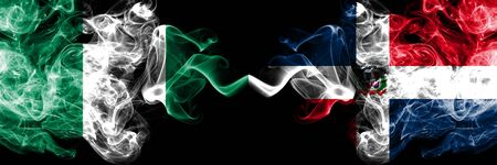 Nigeria vs Dominican Republic abstract smoky mystic flags placed side by side. Thick colored silky smoke flags of Nigerian and Dominican Republic