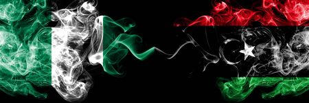 Nigeria vs Libya, Libyan abstract smoky mystic flags placed side by side. Thick colored silky smoke flags of Nigerian and Libya, Libyan