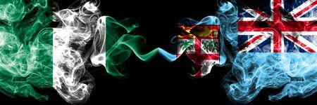 Nigeria vs Fiji abstract smoky mystic flags placed side by side. Thick colored silky smoke flags of Nigerian and Fiji