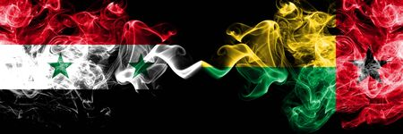 Syria vs Guinea Bissau smoke flags placed side by side. Thick colored silky smoke flags of Syrian and Guinea Bissau Stock Photo