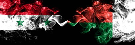 Syria vs Madagascar, Madagascan smoke flags placed side by side. Thick colored silky smoke flags of Syrian and Madagascar, Madagascan Stock Photo