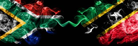 South Africa vs Saint Kitts and Nevis smoky mystic flags placed side by side. Thick colored silky abstract smoke flags concept Stock Photo