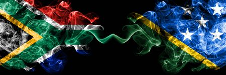 South Africa vs Solomon Islands smoky mystic flags placed side by side. Thick colored silky abstract smoke flags concept
