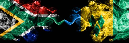 South Africa vs Saint Vincent and the Grenadines smoky mystic flags placed side by side. Thick colored silky abstract smoke flags concept