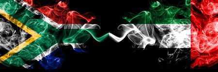 South Africa vs United Arab Emirates, Emirati smoky mystic flags placed side by side. Thick colored silky abstract smoke flags concept