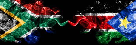 South Africa vs South Sudan smoky mystic flags placed side by side. Thick colored silky abstract smoke flags concept