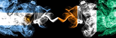 Argentina vs Ivory Coast smoky mystic fire flags placed side by side. Thick colored silky abstract smoke flags concept