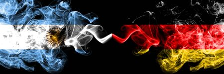Argentina vs Germany, German smoky mystic fire flags placed side by side. Thick colored silky abstract smoke flags concept
