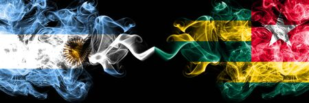 Argentina vs Togo, Togolese smoky mystic fire flags placed side by side. Thick colored silky abstract smoke flags concept Stock Photo