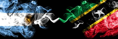 Argentina vs Saint Kitts and Nevis smoky mystic fire flags placed side by side. Thick colored silky abstract smoke flags concept Stock Photo