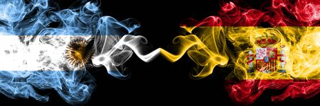 Argentina vs Spain, Spanish smoky mystic fire flags placed side by side. Thick colored silky abstract smoke flags concept 版權商用圖片