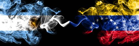 Argentina vs Venezuela, Venezuelan smoky mystic fire flags placed side by side. Thick colored silky abstract smoke flags concept