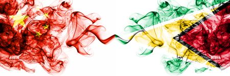China, Chinese vs Guyana, Guyanese smoky mystic states flags placed side by side. Concept and idea thick colored silky abstract smoke flags