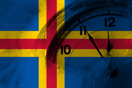 Aland, Alandic flag with clock close to midnight in the background. Happy New Year concept