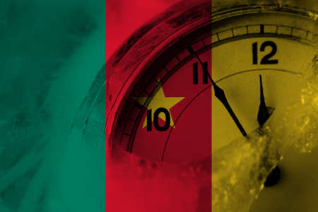 Cameroon, Cameroonian flag with clock close to midnight in the background. Happy New Year concept