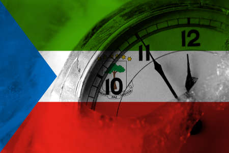 Equatorial Guinea flag with clock close to midnight in the background. Happy New Year concept