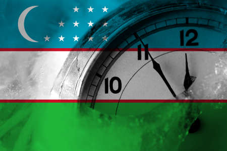 Uzbekistan flag with clock close to midnight in the background. Happy New Year concept