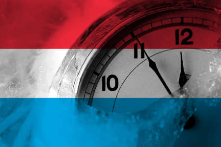 Luxembourg flag with clock close to midnight in the background. Happy New Year concept