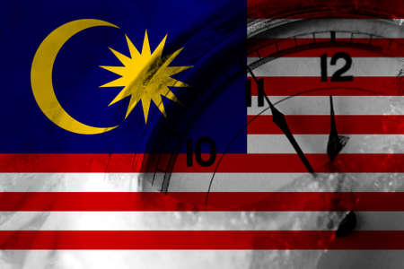 Malaysia, Malaysian flag with clock close to midnight in the background. Happy New Year concept