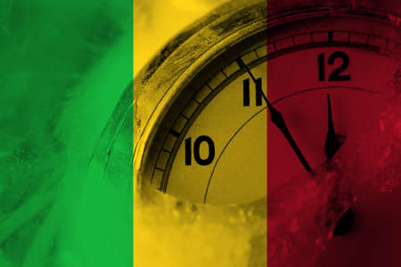 Mali flag with clock close to midnight in the background. Happy New Year concept