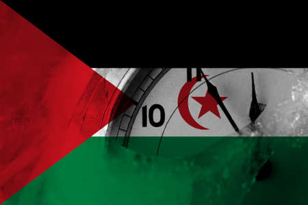 Sahrawi flag with clock close to midnight in the background. Happy New Year concept