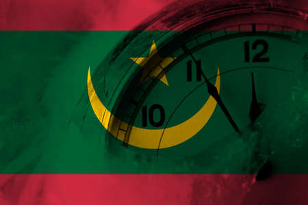 Mauritania flag with clock close to midnight in the background. Happy New Year concept