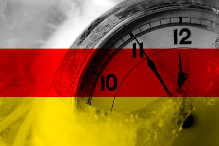 South Ossetia flag with clock close to midnight in the background. Happy New Year concept