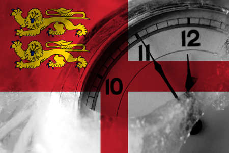 United Kingdom, Great Britain, British, Sark flag with clock close to midnight in the background. Happy New Year concept