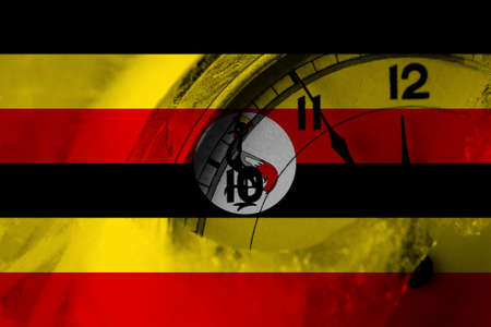 Uganda flag with clock close to midnight in the background. Happy New Year concept