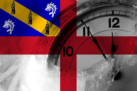 United Kingdom, Great Britain, British, Herm flag with clock close to midnight in the background. Happy New Year concept