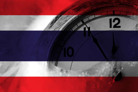 Thailand, Thai flag with clock close to midnight in the background. Happy New Year concept