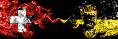 Switzerland, Swiss vs Germany, German, Deutschland, Baden Wurttemberg smoky mystic flags placed side by side. Thick colored silky abstract smoke flags.