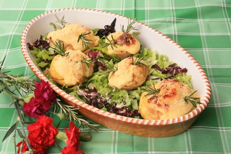 Baked potato halves with cheese in lettuce Stock Photo