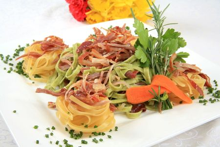 A serving of fresh and delicious pasta with bacon and ham photo