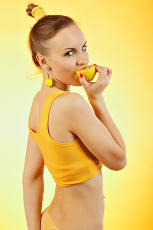 Close up young woman with citrus fruit in studio photo