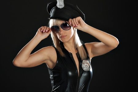 Portrait blondy woman in police girl suit in dark photo