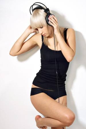 Portret jonge vrouw in de buurt van muur met koptelefoon luisteren muziek