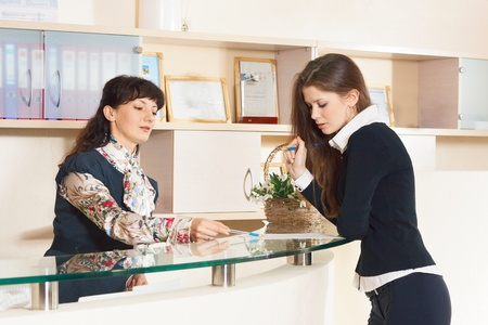 Two woman tolking near help desk in reception office photo