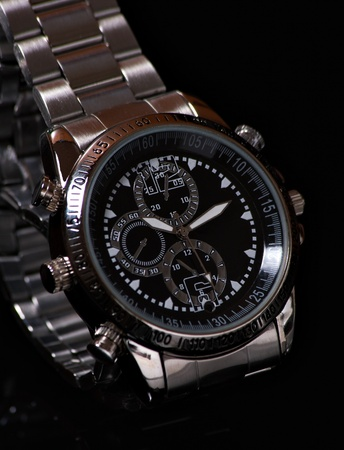 Close up man wristwatch on the black background with reflection