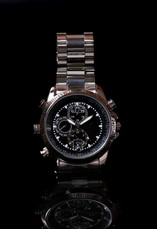 clockwise: Close up man wristwatch on the black background with reflection